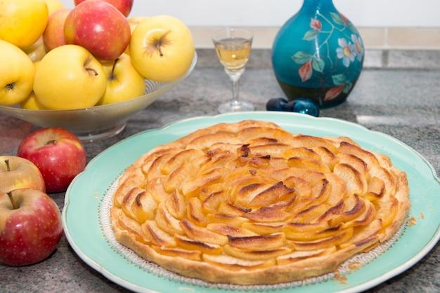Schöner apfelkuchen mit äpfeln und glas