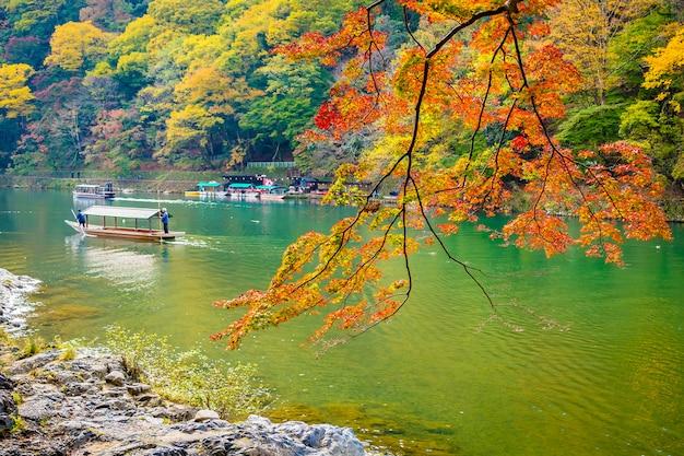 Schöner arashiyama-fluss mit ahornblattbaum und boot um see