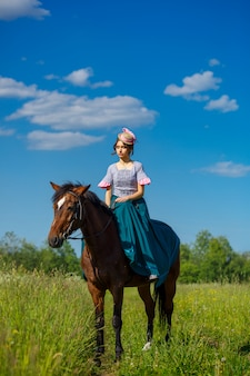 Schöner aristokrat in einem kleid auf einem pferd