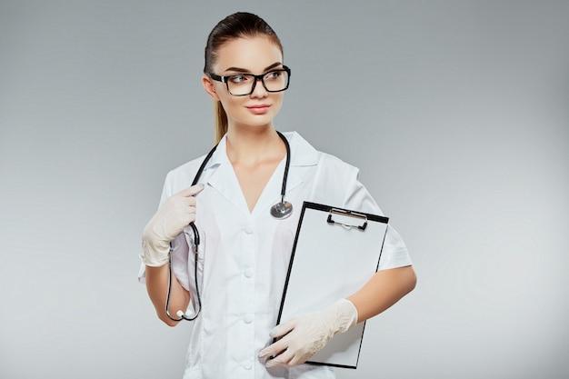 Schöner arzt mit braunen haaren und nacktem make-up, das weiße medizinische uniform, brille, stethoskope und weiße handschuhe am grauen studiohintergrund trägt und notizen hält.