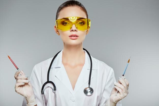 Schöner arzt mit braunen haaren und nacktem make-up, das weiße medizinische uniform, brille, stethoskope und weiße handschuhe am grauen studiohintergrund trägt und spritzen, porträt hält.