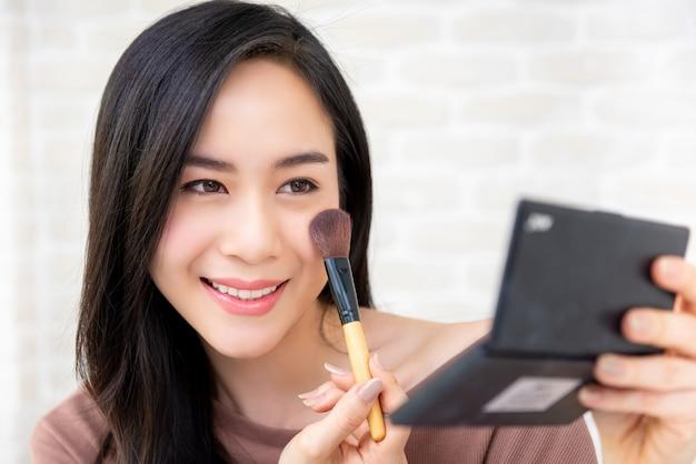 Schöner asiatinschönheit blogger, der kosmetisches make-uptutorial tut