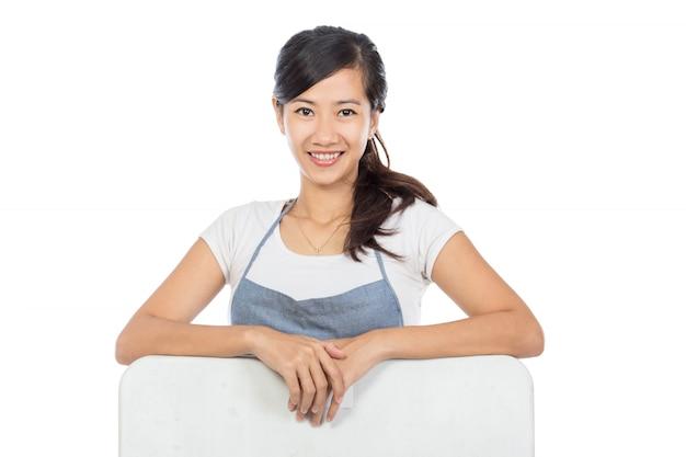 Schöner asiatischer cafébesitzer, der leere weiße tafel hält