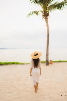 Schöner asiatischer frauenabnutzungshut des porträts mit glücklicher freizeit des lächelns auf dem strand und dem meer in den feiertagsferien