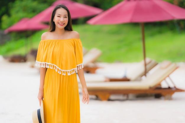 Schöner asiatischer frauenabnutzungshut des porträts mit glücklicher freizeit des lächelns auf dem strandseeozean in den feiertagsferien