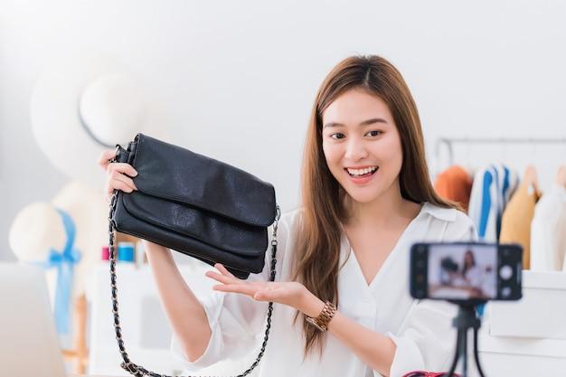 Schöner asiatischer frauenblogger zeigt und wiederholt produkt. vor der smartphonekamera.