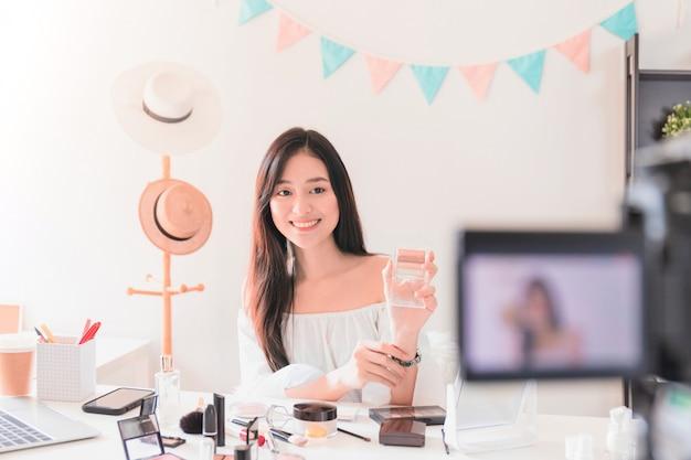 Schöner asiatischer frauenblogger zeigt, wie man kosmetik herstellt und benutzt.