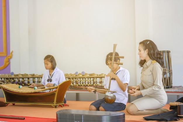 Schöner asiatischer lehrer, der studenten unterrichtet, thailändische instrumente zu üben
