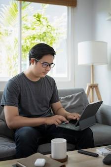 Schöner asiatischer mann, der auf dem sofa sitzt und online mit computertablette arbeitet.