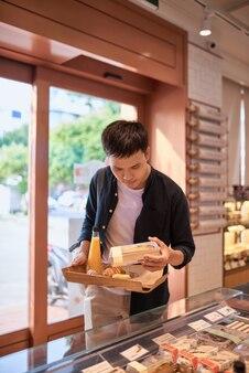 Schöner asiatischer mann, der nachmittags eine bäckerei für eine kaffeepause kauft. bäckerei und kaffeepause.