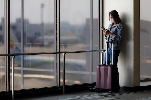 Schöner asiatischer reisender, der hygieneschutzmaske trägt, die allein steht und ein smartphone am flughafen verwendet, während auf einen flug wartet. idee für das reisen in einer neuen normalen situation.