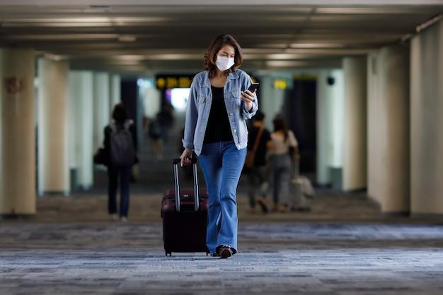 Schöner asiatischer reisender, der hygieneschutzmaske trägt, die gepäcktasche geht und smartphone im flughafenterminal verwendet. idee für ein neues normales reisen.