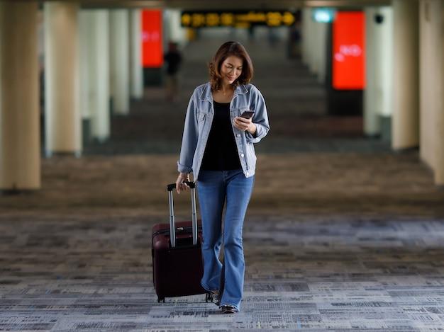 Schöner asiatischer reisender, der lässige kleid hält tasche mit smartphone und zu fuß in flughafenterminal gehweg trägt.