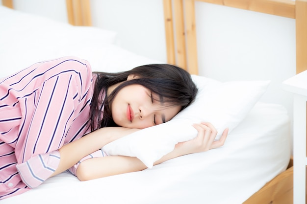 Schöner asiatischer schlaf der jungen frau, der im bett liegt