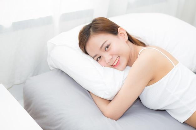 Schöner asiatischer schlaf der jungen frau des porträts, der im bett liegt