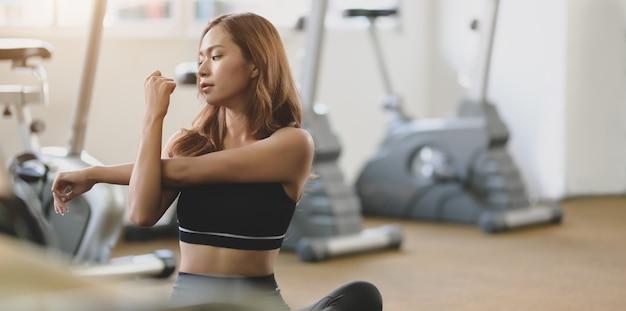Schöner asiatischer weiblicher athlet, der arme nach übung ausdehnt