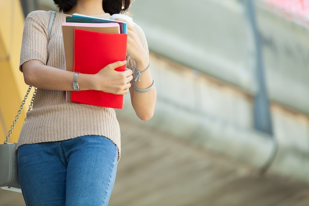 Schöner asiatischer weiblicher student, der ihre bücher und einen tasse kaffee hält