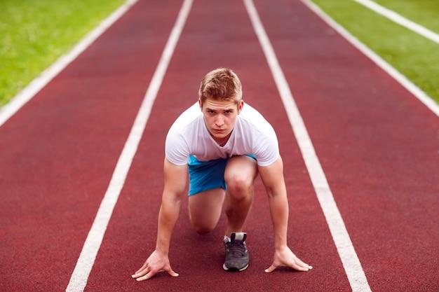 Schöner athlet auf einer rennstrecke ist bereit zu laufen