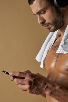 Schöner athlet mit muskulösem körper, der nachricht auf dem handy schreibt