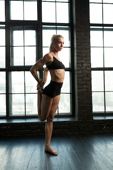 Schöner athletischer blonder tänzer und sportlerin mit dem schönen muskulösen körper, der übungen nahe ausdehnend tut