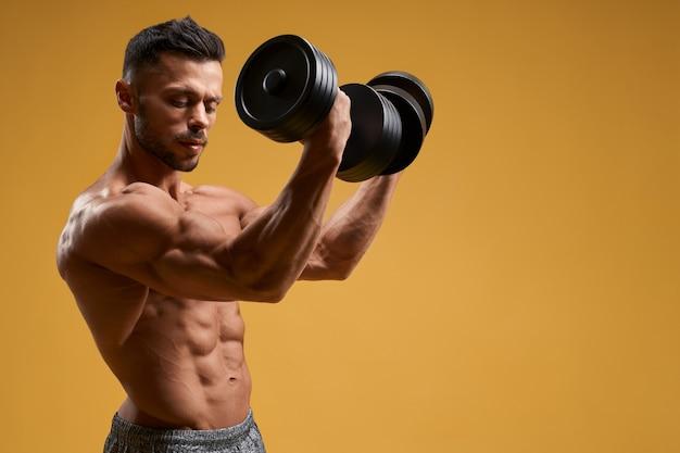 Schöner athletischer mann, der armmuskeln aufpumpt
