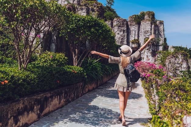Schöner aufgeregter blondinewanderer geht und bewundert tropische landschaften im paradiesinselhotel in sanya, china. rückansicht