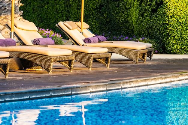 Schöner außenpool mit liegestuhl und sonnenschirm im resort für reisen und urlaub