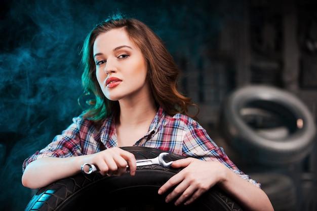 Schöner automechaniker. schöne junge frau mit arbeitswerkzeug und blick in die kamera, während sie sich in der autowerkstatt an den autoreifen lehnt