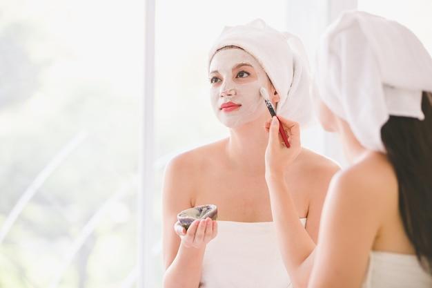 Schöner badekurort der jungen frau und des freunds, der kosmetische maskencreme auf dem gesicht sich entspannt empfängt massage anwendet
