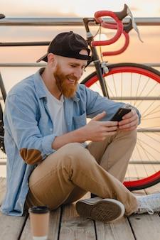 Schöner bärtiger hipster-mann, der smartphone verwendet, das mit fahrrad im morgensonnenaufgang durch das meer reist, gesunder reisender des aktiven lebensstils