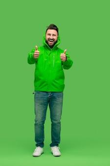 Schöner bärtiger junger mann, der kamera lokalisiert auf grün betrachtet
