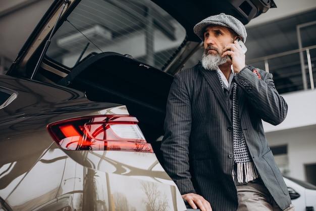Schöner bärtiger mann, der telefon benutzt und am auto steht