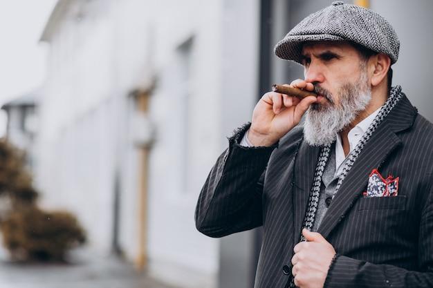 Schöner bärtiger mann, der zigarette raucht