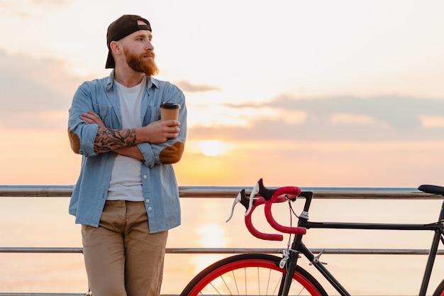 Schöner bärtiger mann des ernsthaften hipster-stils, der jeanshemd und mütze mit fahrrad im morgensonnenaufgang durch das meer trägt, das kaffee trinkt, gesunder reisender des aktiven lebensstils