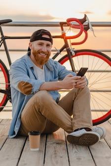 Schöner bärtiger mann des hipster-stils, der jeanshemd und kappe hält smartphone mit fahrrad im morgensonnenaufgang durch das meer, das kaffee trinkt, gesunder reisender des aktiven lebensstils trägt