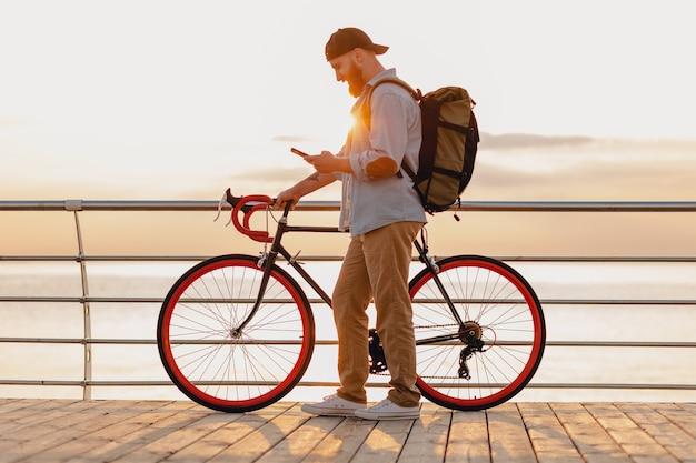 Schöner bärtiger mann des hipster-stils, der mit rucksack auf fahrrad unter verwendung des telefons im morgensonnenaufgang durch das meer reist, gesunder aktiver lebensstil