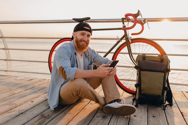 Schöner bärtiger mann des hipster-stils mit rucksack, der das smartphone hält, das jeanshemd und mütze mit fahrrad im morgensonnenaufgang durch das meer gesunder aktiver lebensstil reisender rucksacktourist trägt