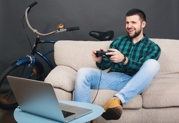 Schöner bärtiger mann des jungen hipsters, der zu hause auf der couch sitzt und videospiel auf notizbuch spielt