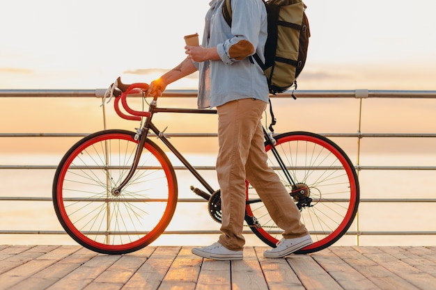 Schöner bärtiger mann im hipster-stil mit rucksack, der jeanshemd und mütze mit fahrrad im morgensonnenaufgang durch das meer trägt, das kaffee trinkt, gesunder aktiver lebensstil reisender rucksacktourist