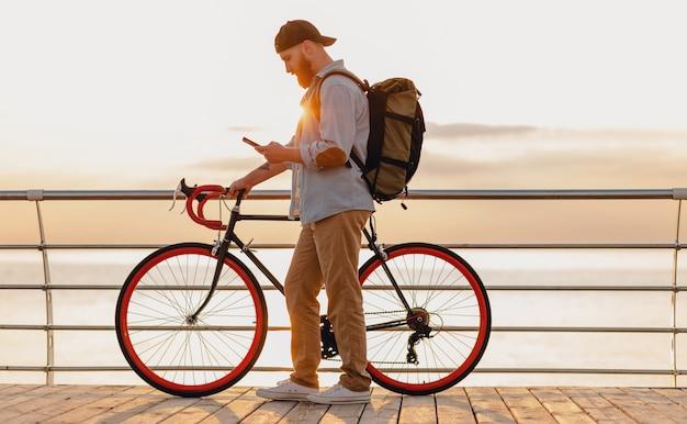 Schöner bärtiger mann im hipster-stil mit rucksack, der jeanshemd und mütze trägt, die mit fahrrad im morgensonnenaufgang durch das meer reisen, das kaffee trinkt, gesunder aktiver lebensstil reisender rucksacktourist