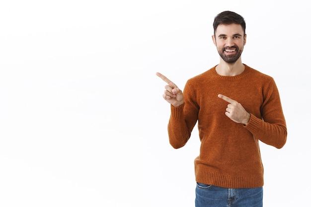 Schöner bärtiger mann im sweatshirt, der mit den fingern auf den kopienraum zeigt, lächelt zufrieden, ratschläge zum kauf eines abonnements, klicken sie auf den link oder folgen sie der seite, um informationen zu erhalten, weiße wand