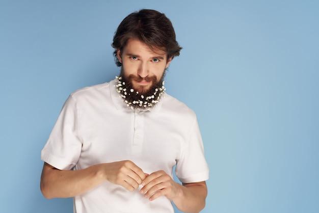 Schöner bärtiger mann mit blumen in seinem weißen hemd im modernen stil haarpflege