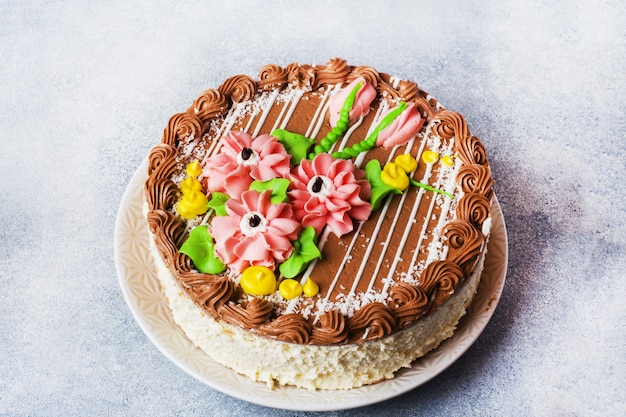 Schöner baiserkuchen mit cremefarbenen rosen verziert. süßwarengeschäft. speicherplatz kopieren.