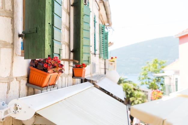 Schöner balkon mit roten blumen im mehrfamilienhaus