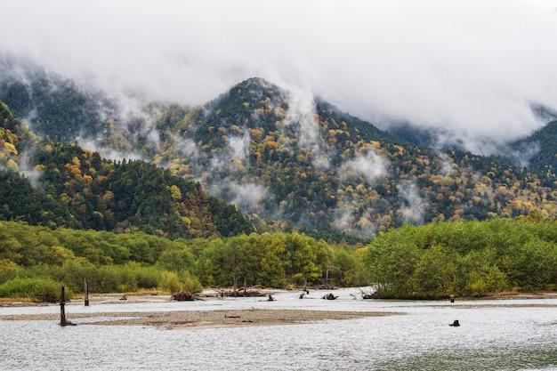 Schöner berg im herbstblatt mit fluss, kamikochi, nationalpark in den nordjapanischen alpen der präfektur nagano, japan.