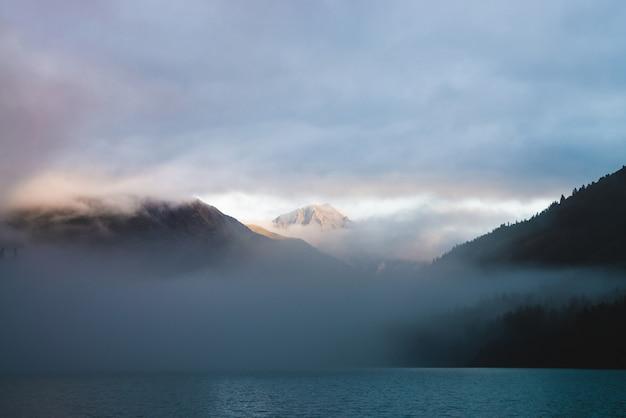 Schöner bergsee zwischen riesigen bergen und wald im nebel in der goldenen stunde. sonnenfarben dichten tiefe wolken. großer stein glitzert bei sonnenaufgang. bunte alpine entspannende landschaft mit nebel in pastelltönen.