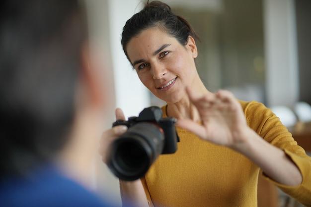 Schöner berufsfotograf, der fotos eines modells macht