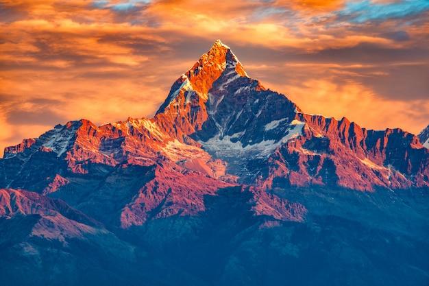 Schöner bewölkter sonnenaufgang in den bergen mit schneekante vom himalaja-standpunkt, pokhara nepal