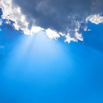 Schöner blauer himmel mit sonnenstrahlen und wolken. sonnenstrahlen.