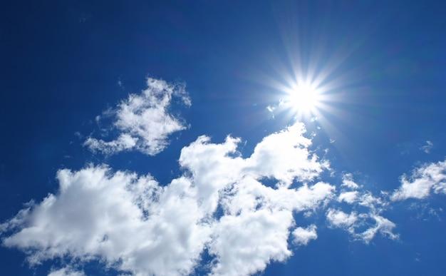 Schöner blauer himmel mit weißen wolken und sonnenreflexion.
